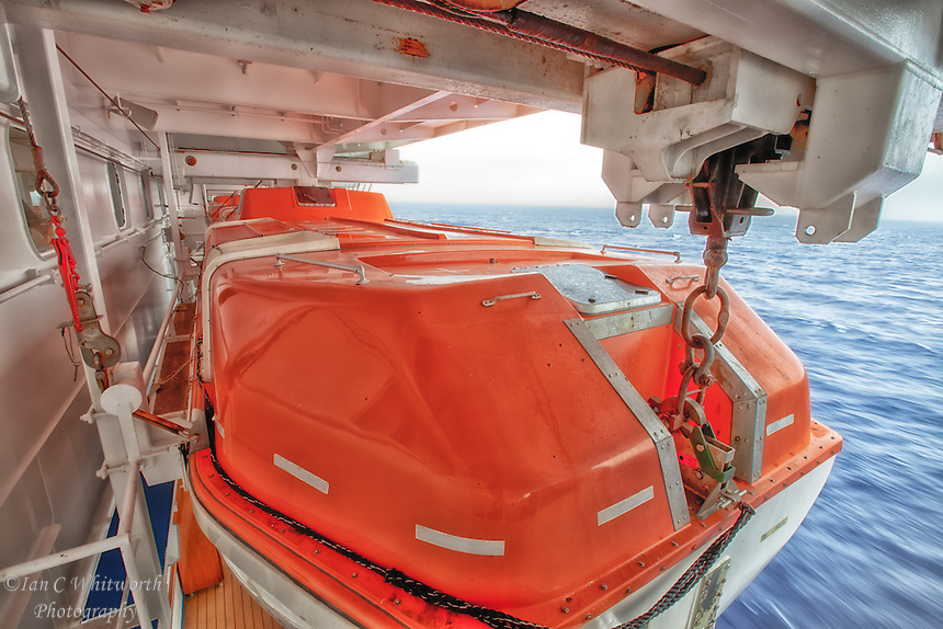 A view over looking the lifeboats onboard a cruise ship cruising the caribbean.