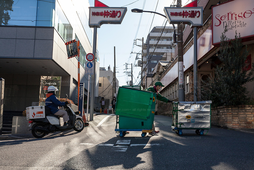"""A worker for Yamato """"Kuroneko"""" (Black Cat) delivery company pushes trolleys containing parcels to be delivered in a back street near Waseda in Tokyo. Japan. Thursday January 9th 2015"""