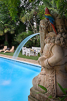 A hand-painted parrot sits on the head of a water feature in the form of a Hindu god overlooking the outdoor swimming pool