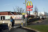"""Dublin, Ireland, January 6, 2011:.Young boys riding their horses by Mc Donald's on Bell Camp housing estate..Since the beginning of crisis, between 10 and 20 thousand horses have become homeless or went in the hands of the youths in urban areas. Lots of Irish people who used to buy horses for fun during the boom years of """"Celtic Tiger"""", now are abandoning them faced with expenditure of 35 Euro a week to properly maintain a horse. This animal previously worth 2000 Euro now can be purchased for as little as 80 Euro. New owners keep their horses in city greens, city ruins, or their house gardens, in very bad conditions. Most do not get much food, many are starving, dying, being mistreated..(Photo by Piotr Malecki / Napo Images)..Dublin, Irlandia, 6/01/2011:.Chlopcy jada konno kolo Mac Donalda na osiedlu mieszkaniowym Bell Camp..Od poczatku kryzysu od 10 do 20 tysiecy koni zostalo wyrzuconych na ulice przez wlascicieli nie chcacych placic okolo 35 Euro/tydzien za ich utrzymanie. Wpadaja one czesto w rece mlodziezy z ubogich dzielnic miasta, ktora handluje nimi, bije, glodzi, trzyma w skrajnie trudnych warunkach, w przydomowych ogrodkach lub ruinach budynkow i szaleje na nich po miescie. Kon, ktory byl wart 2000 Euro teraz moze byc kupiony za 80. .Fot: Piotr Malecki / Napo Images."""
