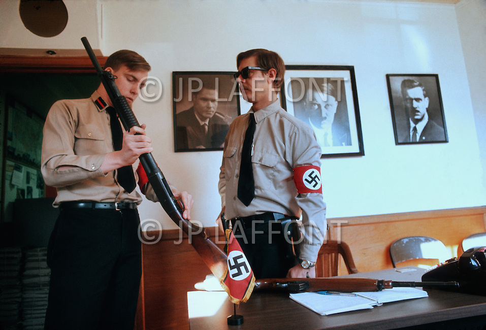February 10, 1972, Arlington, Virginia. Two members of the White National Socialist Party at a desk inspecting some weapons. Above their heads, on the left a picture of Rockwell, the founder of their Party, then a portrait of Adolf Hitler, and a portrait of Matt Koehl, the Commander of the Party.