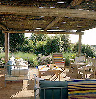 The loggia is furnished with a mixture of painted metal daybeds and wooden chairs beneath a shady pergola