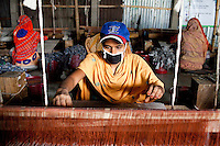 Murunnahar Khatun (in blue hat), works on a rug at the Mornia Kik Rug Factory in Doani Villlage, Haragach Upazila, Rangpur, Bangladesh on 19th September 2011 where she works alongside 25 rural village women making rugs for German textile discounter Kik. Over 400 women have been economically empowered through the CARE Bangladesh WONDER Project that was completed recently. The WONDER Project's goals were to create sustainable income and employment opportunities for extremely poor women by training them in rug production for export. The women now earn about 4000 Bangladeshi Taka per month. The WONDER Project has now moved into a new phase that focusses on general healthcare, workplace safety and nutritional training and awareness programs. Photo by Suzanne Lee for The Guardian