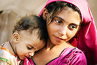 With a maturity beyond her years, eight-year-old 'Mother Mary' figure Khailzabina comforts her baby brother Faisal Khan (18 months) who is suffering from heat stroke in the 50 degree heat. <br /> <br /> North Western Frontier, Pakistan