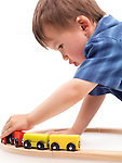 Two year old boy plaing with a wooden toy train on a railroad isolated on white background