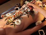 Person taking sushi rolls served on a beautiful nude asian woman's body. Japanese Nyotaimori.