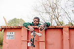 Lonnie Holley creates art from found objects. He searches for objects to add to a new art piece in a dumpster in Atlanta, Georgia, December 12, 2012. He found a softball, a baseball, and some other items.