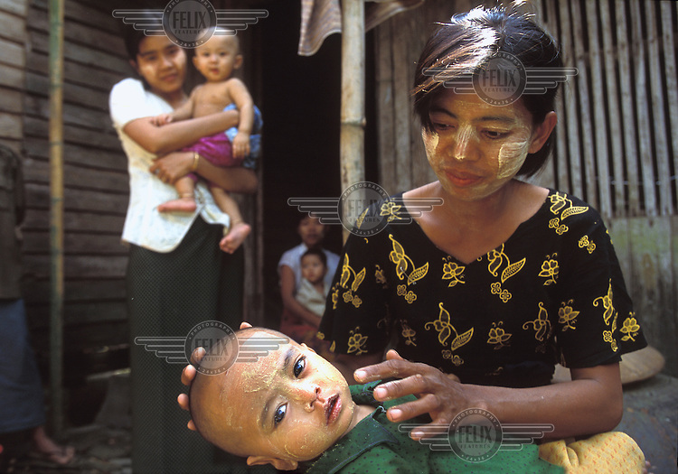"""Traditional """"tanaka"""" is applied to a baby's face in Khat-Tu village. Tanaka is believed to be good for the skin and keep away germs and evil spirits. All Burmese women and children wear tanaka, which is made by grinding the bark of sandalwood."""