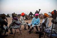 Camel owners sitting at a tea stall at Pushkar fair ground.  Rajasthan, India.