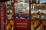 _SM14429, Russia, 2010, RUSSIA-10079. A vendor reads in her shop.<br />