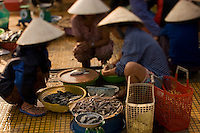 Vietnamese women clean fish in a Hoi An market before selling them