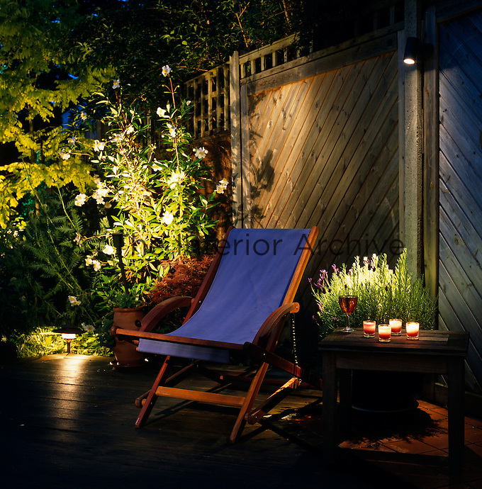 In the garden at night; a mixture of tealights and spotlights have created this enticing corner