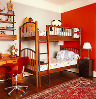 One wall of the child's bedroom furnished with bunk beds is painted a vibrant red