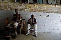 Cuban men, the Afro-Cuban religion belivers, sitting in a passage of the old house in Havana, Cuba, August 11, 2009. The Palo religion (Las Reglas de Congo) belongs to the group of syncretic religions which developed in Cuba amongst the black slaves, originally brought from Congo during the colonial period. Palo, having its roots in spiritual concepts of the indigenous people in Africa, worships the spirits and natural powers but can often give them faces and names known from the Christian dogma. Although there have been strong religious restrictions during the decades of the Cuban Revolution, the majority of Cubans still consult their problems with practitioners of some Afro Cuban religion.