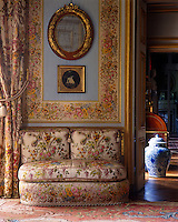 A banquette is upholstered in a beautiful floral fabric echoed in the curtain and fabric frieze on the wall behind