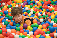 Happy Caucasian Kid Boy in Playground with Colorful Toy Balls