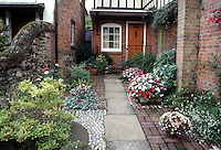 Courtyard container garden, mixed hardscaping stone, brick pebbles, house, small space garden with annuals impatiens, perennial ivy vines, shrubs, for curb appeal