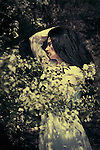 atmospheric photo of beautiful young caucasian woman with long black hair in white wedding dress in dappled sunlight