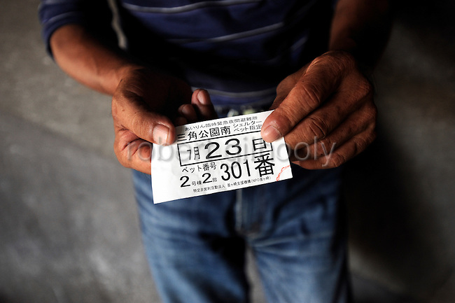 """Koji"" Yamaguchi, a day laborer who has no fixed abode of residence, shows the ticket he received indicating his bed number at a shelter in the Kamagasaki district of Osaka, Japan."