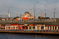General view of Galata Bridge, 1994, Istanbul, Turkey with Suleymaniye Mosque in the background. The Galata bridge, the fifth between Karakoy and Eminonu, was built by STFA and designed and supervised by GAMB. It is a 490 m long bascule bridge, with a main span of 80 m, and a 42 m wide deck and has 3 traffic lanes and one walkway in each direction plus tram tracks connecting suburban  Zeytinburnu to Kabatas. Picture by Manuel Cohen.