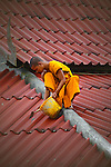 Very unusual sight of a Thai Monk repairing a leaking temple roof in Tak province, Thailand.
