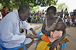 As other patients wait in the background, John Nyolina examines a child in Nimule, South Sudan, during a mobile clinic run by Caritas of the Diocese of Torit. Nyolina is a clinical officer, the equivalent of a physician's assistant. The mobile clinic was launched in January 2014 shortly after war broke out within South Sudan, and thousands of families arrived in this area, near the country's border with Uganda, from Bor, in Jonglei State. Yet many have not been warmly welcomed to this region of Eastern Equatoria State, where two earlier waves of displaced people in the 1980s and 1990s left relations tense between the newcomers, who are Dinka, and the largely Ma'adi residents around the city of Nimule. The ACT Alliance is helping the displaced families and the host communities affected by their presence, and is supporting efforts to reconcile the two groups. The ACT Alliance also supports the Caritas mobile clinic, which provides medical care--often under a tree--both to displaced families as well as to poor residents of the host communities.