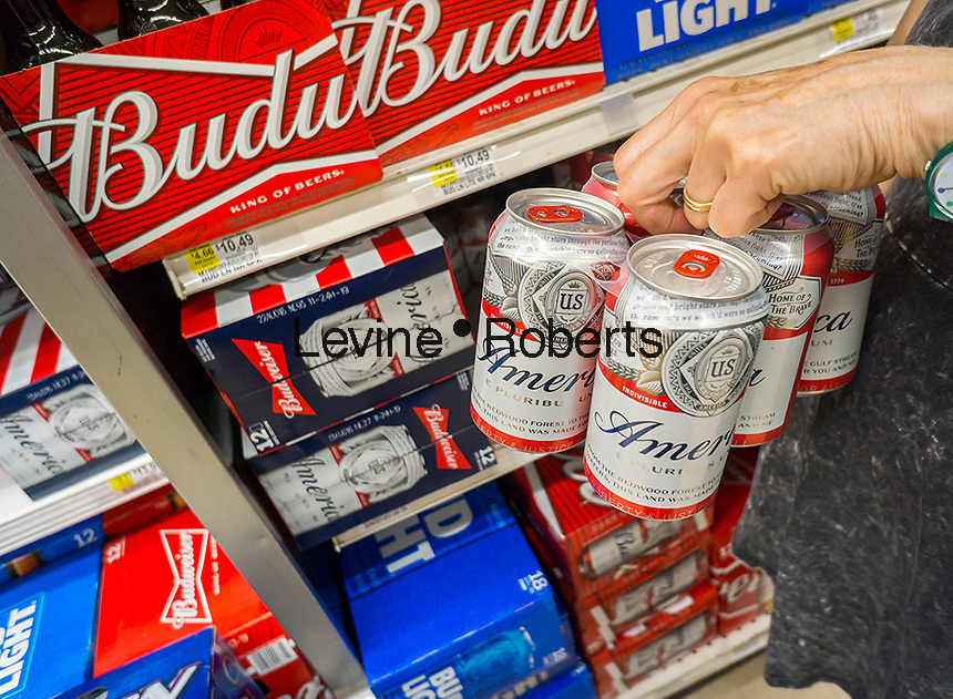 "A shopper chooses a six-pack of Budweiser beer featuring the ""America"" name instead of Budweiser on Saturday, May 28, 2016. Besides branding the beer ""America"" the label features other patriotic slogans and is temporary for  the summer. AB InBev is owned by a Brazilian and Belgium conglomerate. (© Richard B. Levine)"