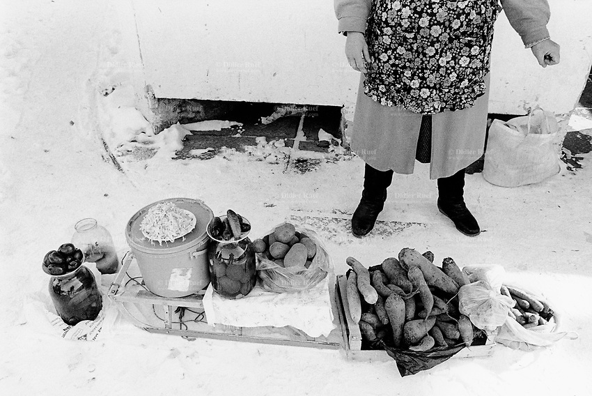 Ukraine. Province of Kiev. Slavutich. Vegetable stall in the food market. Saleswoman wearing an apron full of flowers. Radiations pass through the food chain into the human body and cause health problems. The town of Slavutich was created after the catastrophe which took place on april 1986 at 1.23 am with the explosion of reactor No 4 at Chernobyl atomic power station. Slavutich is distant 60 km from the power station and was newly built after the evacuation of the inhabitants from both towns of Pripyat and Chernobyl. © 2006 Didier Ruef