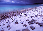 Snow, pebbles and clear blue water of Georgian Bay. Wintertime landscape scenery. Bruce Peninsula National Park, Ontario, Canada.