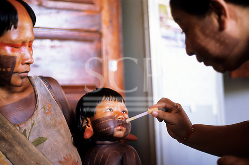 Bacaja village, Amazon, Brazil. Nurse Wanda administers vaccine in drops to baby with his mother in the health post; Xicrin tribe.