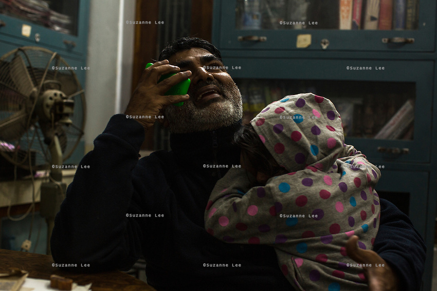 Ajeet Singh, the founder of Guria Swayam Sevi Sansthan speaks on the phone as he cradles Barish, his 5 year old daughter, while he works late into the night in the legal room of Guria office in Varanasi, Uttar Pradesh, India on 14 November 2013.