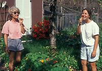 Women picking & eating edible flowers nasturtium in garden