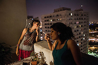 Two young women smoking a cigarette on the balcony of a house. As they are in private they are able to wear T-shirts and their hair uncovered.