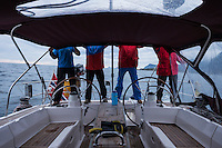 4 people in colorful clothing on the back of a sailboat, Lofoten Islands, Norway