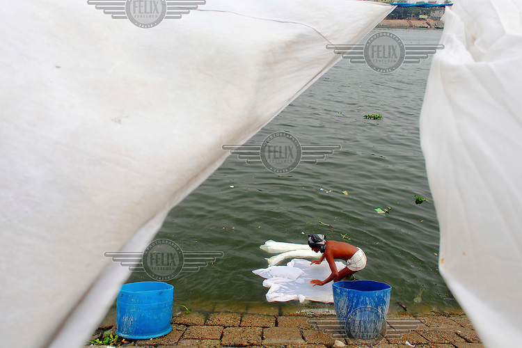 A man washes sheets in the Buriganga River. He was once a fisherman but pollution has killed off aquatic life in the river forcing fishermen to find other work. However the river is dirty and even standing in it can result in skin diseases. Everyday 1.5 million cubic metres of waste water from 7,000 industrial units in surrounding areas and another 0.5 million cubic metres from other sources are released into the river. Although the government have enacted laws that require industry to safely process effluents these are rarely enforced and pollution remains uncontrolled. The river is biologically dead and increasingly a serious health hazard to those using and living near it.