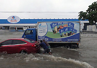 Two men push a car through a flooded road in Recife, Brazil where heavy rain has caused serious flooding ahead of the USA vs Germany World Cup match this afternoon