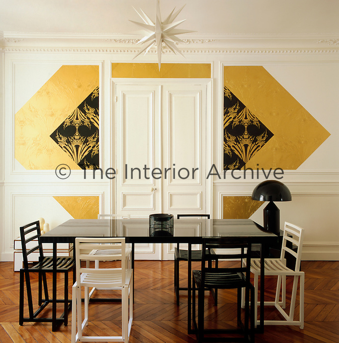 Graphic patterns, added to a simple palette of white, black and gold  creates an elegant combination, whilst the contemporary furniture contrasts with the original period features in this Paris apartment. The dining room is spacious and minimal with simple black and white furniture