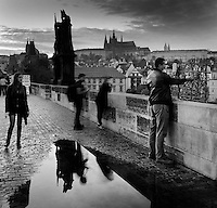 A man touching the bronze relief of St John of Nepomuk on the Charles Bridge or Karluv most, built 1357 - 15th century over the Vltava river, with St Vitus Cathedral and Prague Castle in the distance, Prague, Czech Republic. In 1393, the Bohemian king Wenceslaus ordered St John of Nepomuk (the country's patron saint) thrown off the Charles Bridge because he would not reveal the confessions of the queen. This site on the bridge marks the spot he was thrown. It has become traditional to touch the bridge here to bring good luck and to ensure that the visitor will return to the city of Prague. The historic centre of Prague was declared a UNESCO World Heritage Site in 1992. Picture by Manuel Cohen
