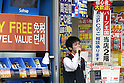 July 1, 2010 - Tokyo, Japan - A salesman for an electronics store is seen beside promotional signs written in Chinese in Akihabara district, Tokyo, Japan, on July 1, 2010. On Tursday, Japan will significantly relax visa requirements for Chinese citizens to attract an increasing number of big-spending Chinese tourists to boost its economy. Japanese Foreign Minister Katsuya Okada told a press conference earlier that the number of households eligible to visit will increase 10-fold to 16 million a year.