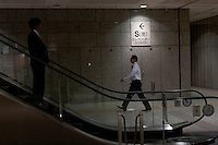 Officer workers on an escalator inside the Tokyo Metropolitan Government Building corridors. Shinjuku, Tokyo, Japan. Friday November 11th 2011