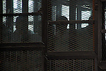 Egyptian defendants of Tahrir Square violence during the fourth anniversary revolution of 25 January stand behind bars at a courtroom, during their trial in Cairo on March 31, 2015. The court acquitted 68 defendants on the charges against them and a fine of 50.000 pounds. Photo by Amr Sayed