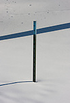 A metal snow fence post bisects a shadow from a nearby tree while creating its own shadow on the snow