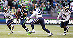 Seattle Seattle Seahawks Russell Wilson (3) scrambles away from St. Louis Rams defensive end Robert Quinn (94), defensive tackle Aaron Donald (99) and cornerback Lamarcus Joyner  (20) after passing during the second quarter  at CenturyLink Field in Seattle, Washington on December 28, 2014. The Seahawks officially wrapped up the No. 1 seed in the NFC playoffs shortly after beating the Rams, 20-6. Despite the Cowboys and Packers also winning to finish 12-4, the Seahawks (12-4) won the multi-team tiebreaker and earned home-field advantage throughout the playoffs for the second consecutive season.  ©2014. Jim Bryant Photo. All Rights Reserved.