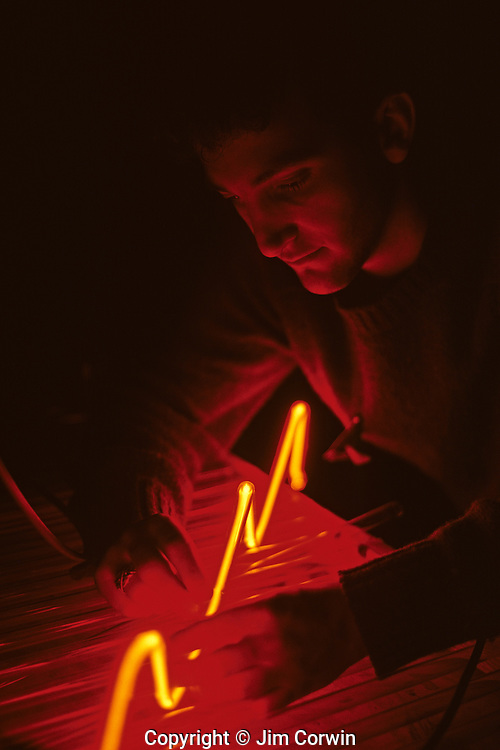 Neon artist working at table in studio with neon tubes