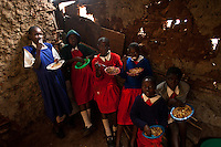 Nairobi, June 2010 -   the older girls take their lunch standing in a  barely together side room off  the one-room school at the  St. Catherine's children's home. F