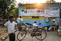 Station operator Raju Lone keeps track as customers gather at the iJal water station to buy drinking water in Gorikathapalli, a remote village in Warangal, Telangana, India, on 22nd March 2015. Safe Water Network works with local communities that live beyond the water pipeline to establish sustainable and reliable water treatment stations within their villages to provide potable and safe water to the communities at a nominal cost. Photo by Suzanne Lee/Panos Pictures for Safe Water Network