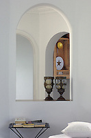 Antique candle-holders are placed in one of the archway windows of the living room