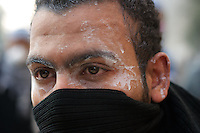 Portrait of an egyptian protestor with the face covered with a mixture of milk and vinegar used to wash out the tear gas shot by the security forces during violent clashes in central Cairo.