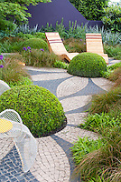 "Fooling the eye in the garden: Rounded shapes and textures in backyard landscape to create Buxus ""flower"" shrubs. Garden chairs, mosaic deck patio, matching color wall, ornamental onions and grasses, landscaping design, purple and green color combination"