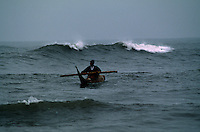 """A young boy paddles a tortora reed boat that fishermen use in the little village north of Lima.  The caballitos, or """"little horses,"""" are the traditional for fishermen in the region."""